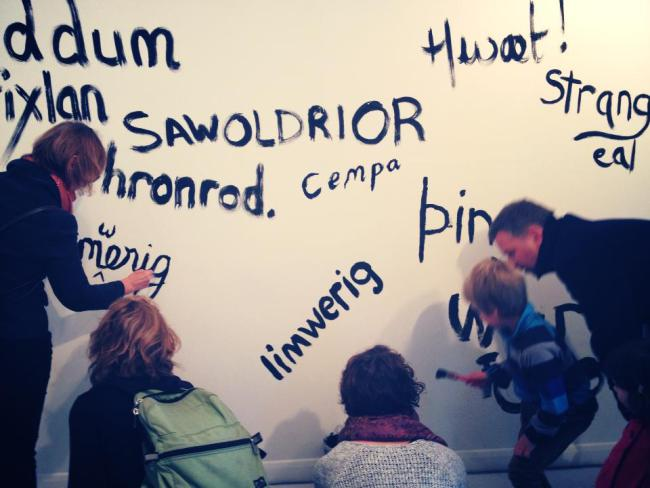 Three adults and two children painting Old English words on a white wall.
