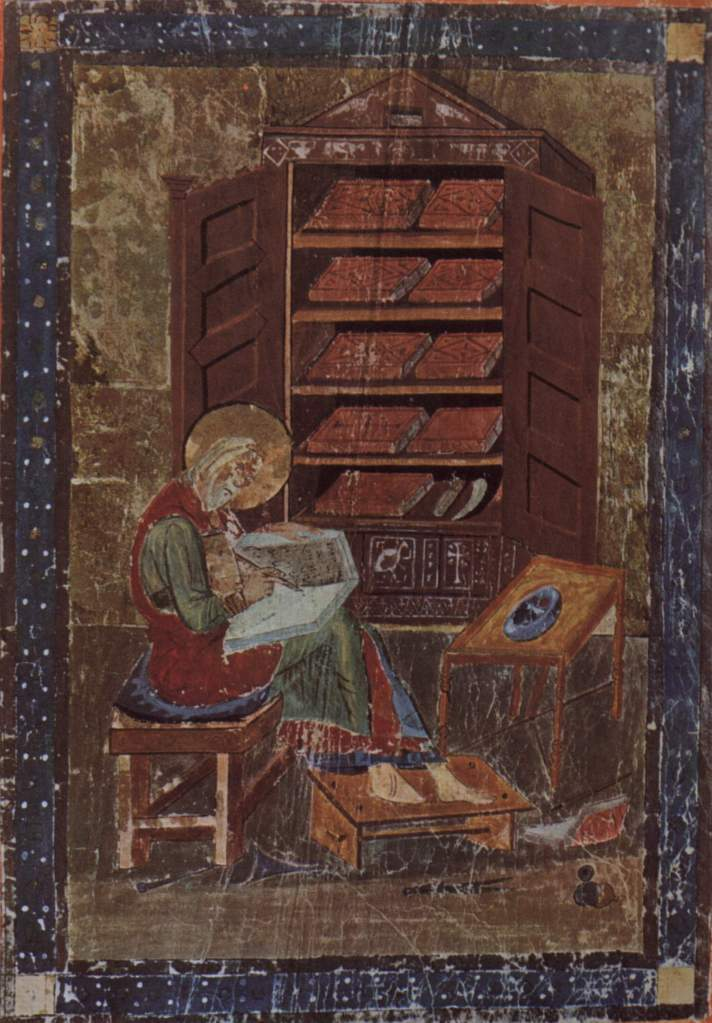 Medieval manuscript image of a man with a halo writing in a book, with a cabinet of books behind him.