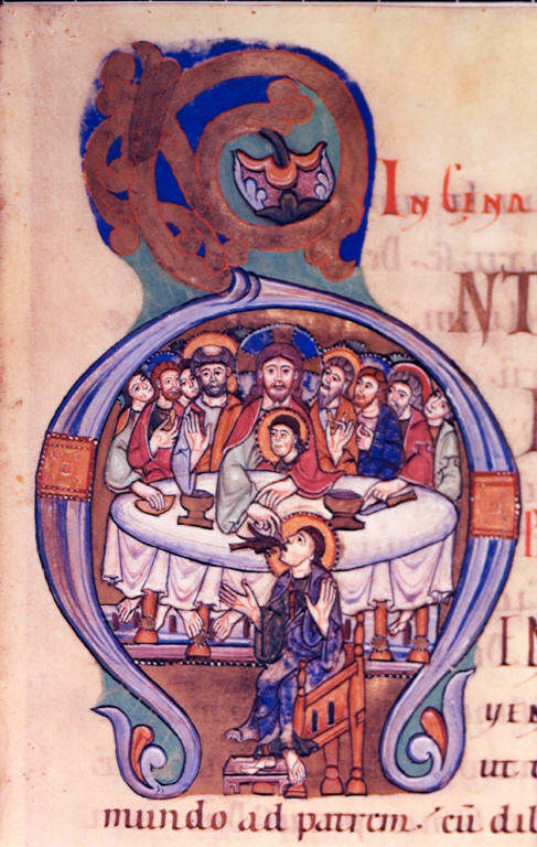 Medieval manuscript image of the letter A showing the Last Supper. Christ passes a sop to Judas who sits on the other side of the table from Christ and the other Apostles. At this moment, Satan, shown here in the form of a black bird, enters Judas.